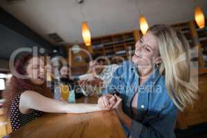 Women arm wrestling and men capturing a shoot