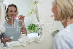 Reflection of woman brushing her teeth