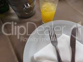 Table with plate and cutlery on napkin