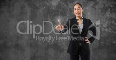 Businesswoman touching air in front of grey wall