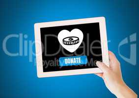 Hand holding tablet with donate button and heart and money icon for charity