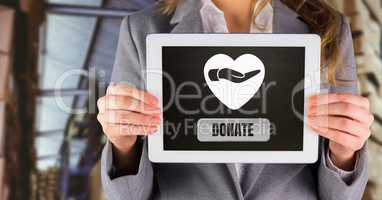 Woman holding tablet with donate button and hand giving with heart for charity