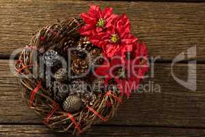 Overhead view of artificial nest with pine cones and poinsettia flowers