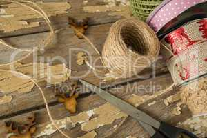 Ribbon roll, scissors and jute rope on wooden table