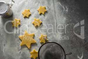 Star shape cookies on flour with strainer