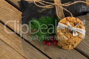 High angle view of cookies with pine needles and cheeries by plastic bag on table