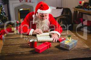 Santa Claus reading scroll in living room