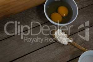 Egg yolk and flour in spoon on a wooden table