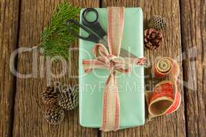 Scissors, pine cones, leaves and ribbon with wrapped gift box on wooden table