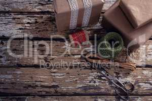 Gift boxes with wrapping material on wooden plank