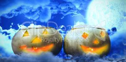 Composite image of illuminated jack o lanterns on table