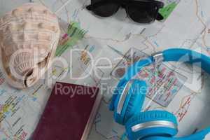 Sunglasses, headphones, passport and seashell on map