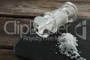 Salt shaker and salt on black slate plate