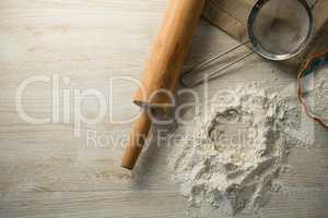Directly above shot of flour in bowl by rolling pin and strainer