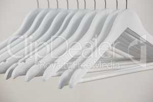 Close-up of white hangers arranged in a row