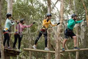 Friends enjoying zip line adventure in park