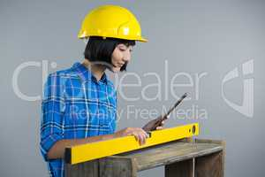 Female architect measuring plywood with engineer scale