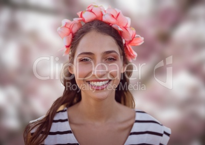 Woman's face in pink forest with leaves and flowers on head