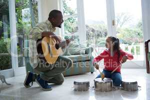 Father and daughter playing with guitar and utensils in living room