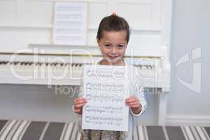 Portrait of cute girl standing with musical sheet
