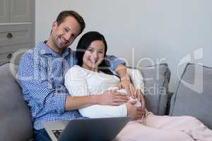 Happy couple feeling the presence of baby in stomach