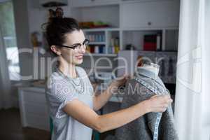 Fashion designer taking measure of fabric