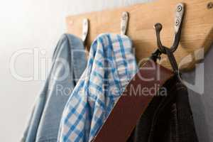 Jeans, denim jacket and shirt hanging on hook