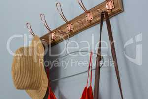 Straw hat, dress and bag hanging on wall