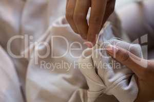 Fashion designer stitching cloth with needle