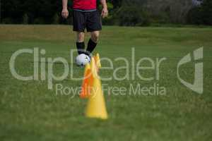 Soccer player dribbling through cones
