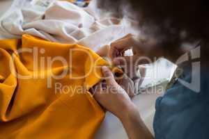 Female fashion designer stitching cloth with needle