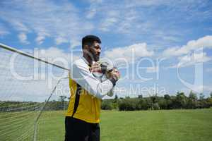 Goalkeeper holding football in front of goal post