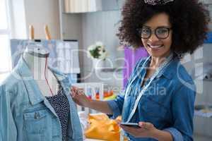 Female fashion designer using mobile phone while designing dress