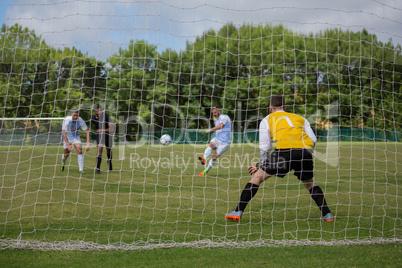 Soccer player kicking ball towards goal post