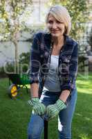 Beautiful woman standing with gardening equipment