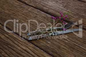 Fork and butter knife with flower on wooden table