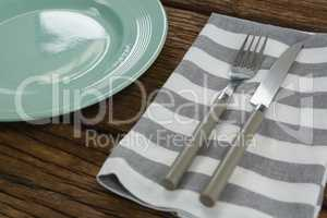 Plate with cutlery and napkin on wooden table
