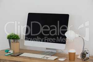 Electric lamp, mobile phone, desktop pc, disposable glass, flora and stationery on table