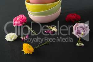 Bowls and flowers arranged on a black themed table