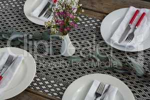 Plates with napkin, fork, butter knife and flower arranged on wooden table