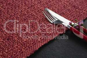 Fork, butter knife with flower on placemat