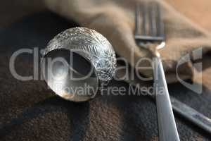 Napkin ring and cutlery on concrete background