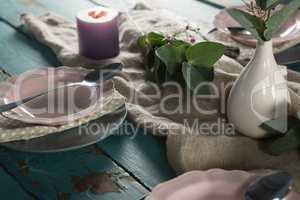 Elegance table setting with flower vase and lit candle