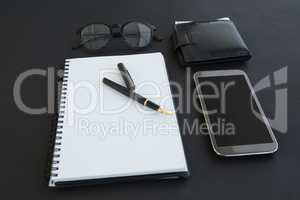 Spectacles, organizer, pen, mobile phone and wallet on background