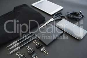T-shirt, pen, wallet, scissors, usb cable, paper clip, mobile phone and digital tablet on black back