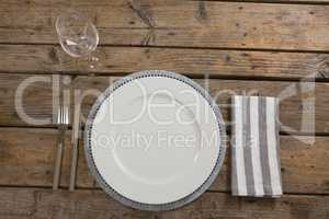 Plate, wine glass, napkin with fork and butter knife on wooden table