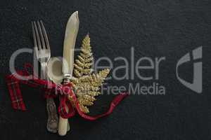 Cutlery with christmas ornament tied up with ribbon