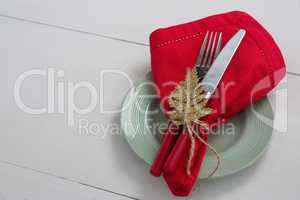 Fork and butter knife with napkin and christmas ornament tied up with a rope