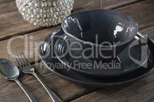 Crockery and cutlery on wooden plank
