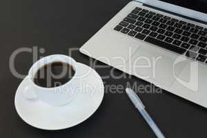 Cup of coffee, laptop and pen on black background